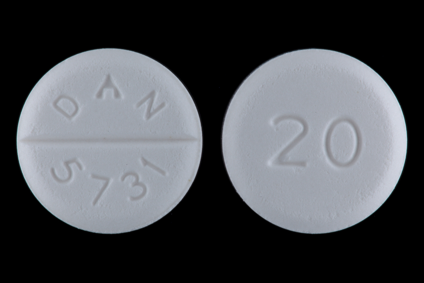 """Two round white 20mg baclofen tablets with """"DAN"""" and """"5731"""" inscribed on one side, and """"20"""" inscribed on the other side."""