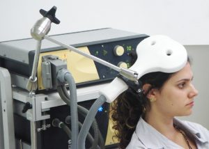 A woman with a magnetic coil placed above the head.